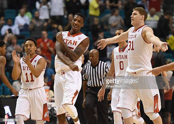 Brandon Taylor Delon Wright and Dallin Bachynski of the Utah Utes celebrate late in their quarterfinal game of the Pac12 Basketball Tournament...