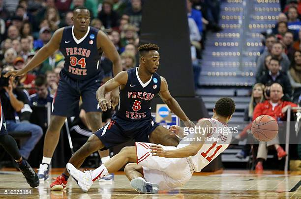 Brandon Taylor of the Utah Utes and Jahmel Taylor of the Fresno State Bulldogs vie for a loose ball in the second half during the first round of the...