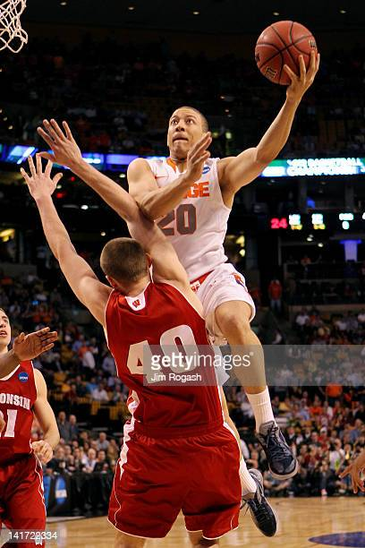 Brandon Triche of the Syracuse Orange draws contact against Jared Berggren of the Wisconsin Badgers while driving to the basket during their 2012...
