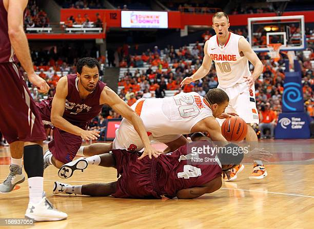 Brandon Triche of the Syracuse Orange falls and loses the ball as teammate Trevor Cooney looks on against Chad Johnson and Damon ShermanNewsoome of...