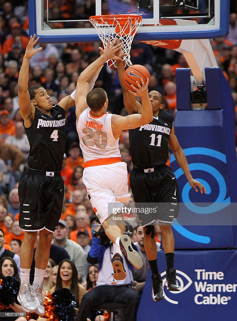 Brandon Triche #20 of the Syracuse Orange goes up for a shot against Josh Fortune #4 and Bryce Cotton #11 of the Providence Friars during the game at the Carrier Dome on February 20, 2013 in Syracuse, New York.
