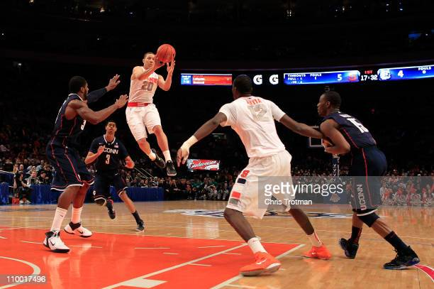 Brandon Triche of the Syracuse Orange looks to pass to Baye Moussa Keita as Alex Oriakhi and Kemba Walker of the Connecticut Huskies defend during...
