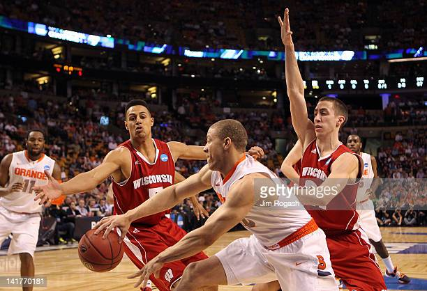 Brandon Triche of the Syracuse Orange passes the ball against Ryan Evans and Josh Gasser of the Wisconsin Badgers during their 2012 NCAA Men's...