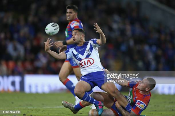 Brandon Wakeham of the Bulldogs is tackled by Shaun Kenny-Dowall of the Newcastle Knights during the round 17 NRL match between the Newcastle Knights...