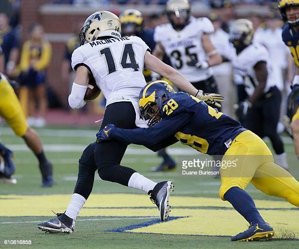 Brandon Watson of the Michigan Wolverines tackles Jay MacIntyre of the Colorado Buffaloes at Michigan Stadium on September 17 2016 in Ann Arbor...