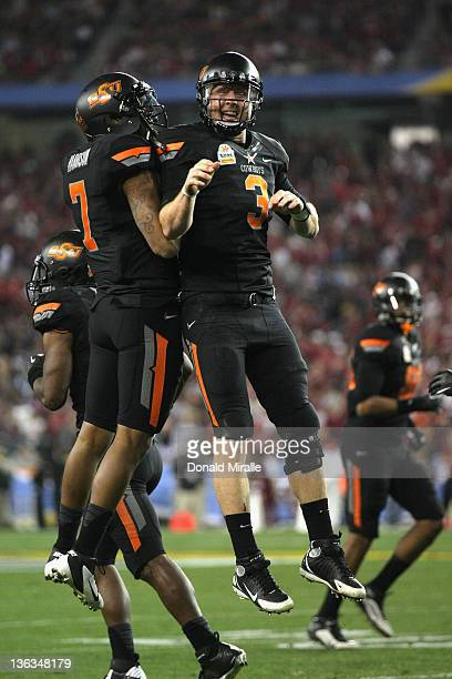 Brandon Weeden and Michael Harrison of the Oklahoma State Cowboys celebrate after Weeden scored a 2yard rushing touchdown in the second quarter...