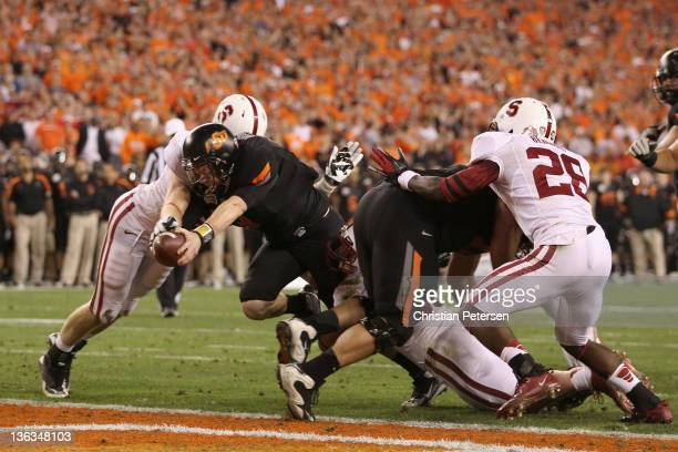 Brandon Weeden of the Oklahoma State Cowboys scores a 2-yard rushing touchdown in the second quarter against the Stanford Cardinal during the...