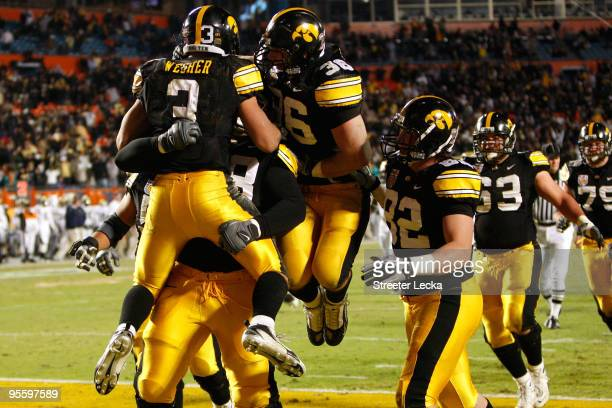 Brandon Wegher of the Iowa Hawkeyes celebrates with his teammates after he scored a 32-yard rushing touchdown late in the fourth quarter against the...