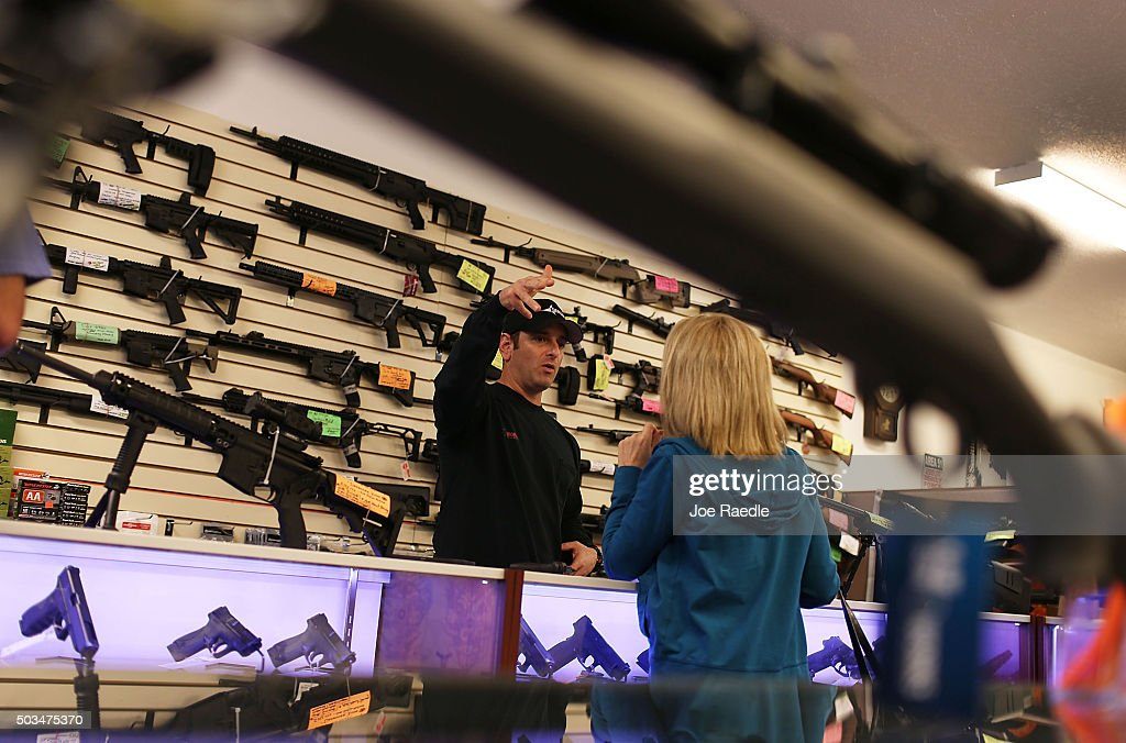 Brandon Wexler (R) helps a customer as she picks up her handguns at the end of the three day waiting period at the K&W Gunworks store on the day that U.S. President Barack Obama in Washington, DC announced his executive action on guns on January 5, 2016 in Delray Beach, Florida. President Obama announced several measures that he says are intended to advance his gun safety agenda.