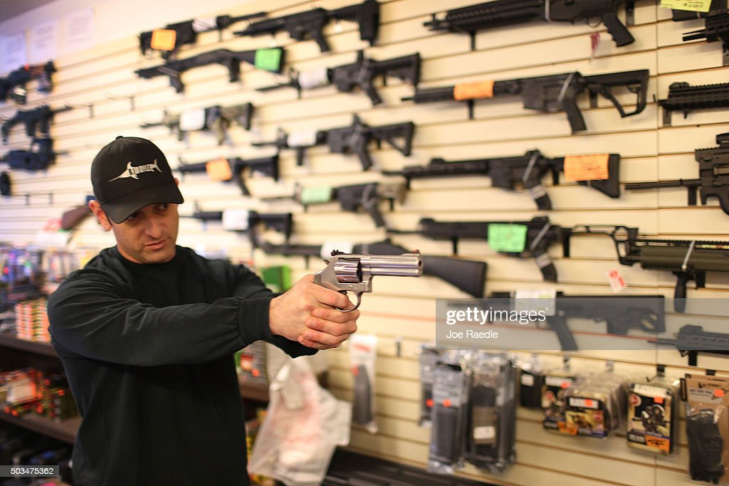 Brandon Wexler shows a customer one of the weapons that she was picking up at the end of the three day waiting period at the K&W Gunworks store on the day that U.S. President Barack Obama in Washington, DC announced his executive action on guns on January 5, 2016 in Delray Beach, Florida. President Obama announced several measures that he says are intended to advance his gun safety agenda.