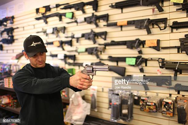 Brandon Wexler shows a customer one of the weapons that she was picking up at the end of the three day waiting period at the KW Gunworks store on the...