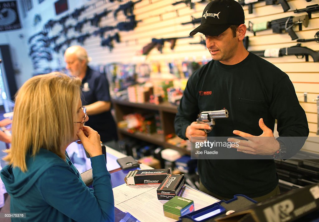 Brandon Wexler (R) shows Cindy Schneider the weapons that she was picking up at the end of the three day waiting period at the K&W Gunworks store on the day that U.S. President Barack Obama in Washington, DC announced his executive action on guns on January 5, 2016 in Delray Beach, Florida. President Obama announced several measures that he says are intended to advance his gun safety agenda.
