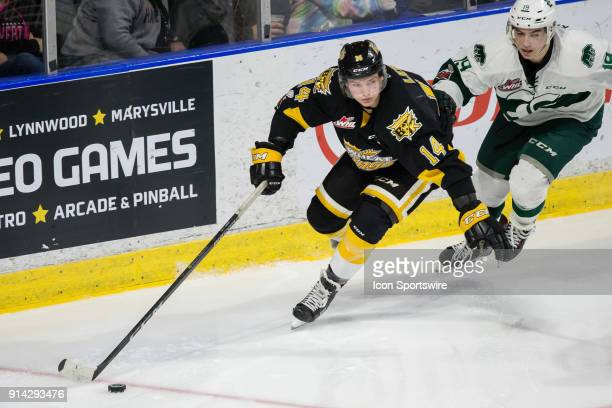 Brandon Wheat Kings forward Ty Lewis skates the puck away from Everett Silvertips forward Bryce Kindopp during the second period in a game between...
