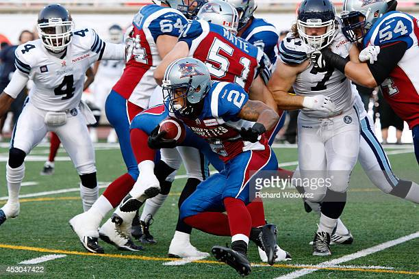Brandon Whitaker of the Montreal Alouettes runs with the ball through a crowd of players during the CFL game against the Toronto Argonauts at...