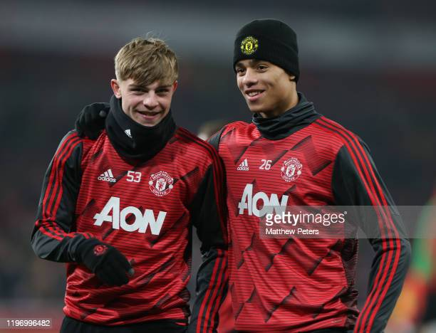 Brandon Williams and Mason Greenwood of Manchester United warm up ahead of the Premier League match between Arsenal FC and Manchester United at...