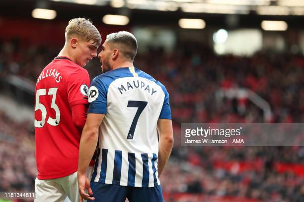 Brandon Williams of Manchester United clashes with Neal Maupay of Brighton and Hove Albion during the Premier League match between Manchester United...