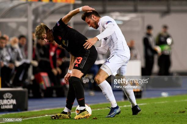 Brandon Williams of Manchester United competes for the ball with Rene Renner of LASK during UEFA Europa League Round of 16 First Leg match between...