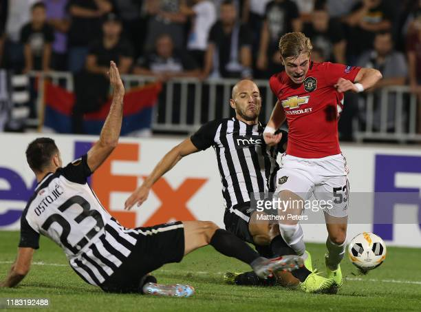 Brandon Williams of Manchester United in action with Nemanja Miletic and Bojan Ostojic of Partizan Belgrade during the UEFA Europa League group L...