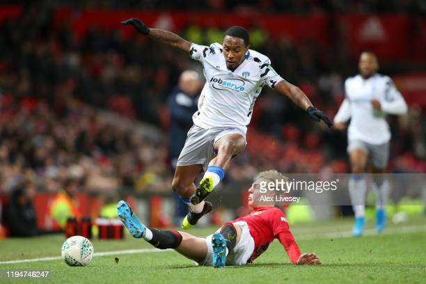 Brandon Williams of Manchester United tackles Callum Harriott of Colchester United during the Carabao Cup Quarter Final match between Manchester...