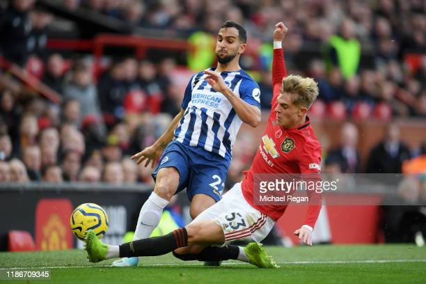 Brandon Williams of Manchester United tackles Martin Montoya of Brighton and Hove Albion during the Premier League match between Manchester United...