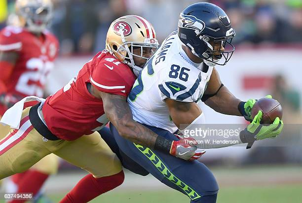 Brandon Williams of the Seattle Seahawks catches a pass over Antoine Bethea of the San Francisco 49ers during the third quarter of their NFL football...