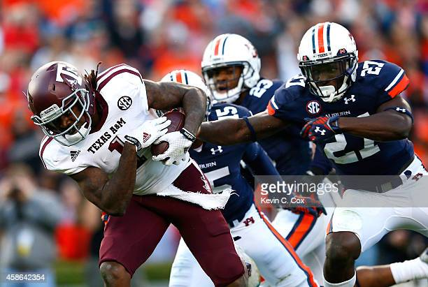 Brandon Williams of the Texas AM Aggies breaks a tackle by Robenson Therezie of the Auburn Tigers at Jordan Hare Stadium on November 8 2014 in Auburn...
