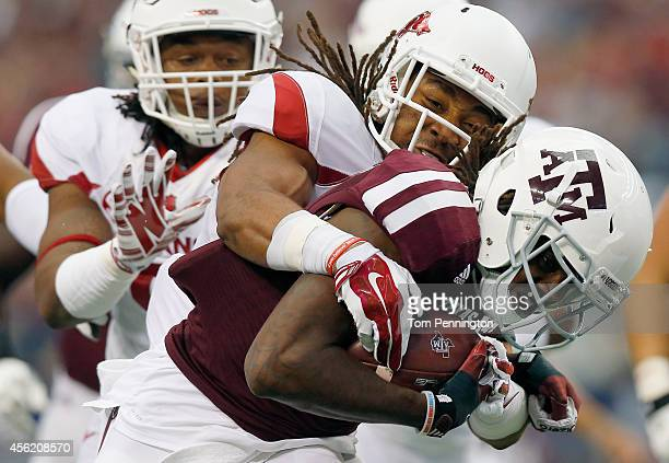 Brandon Williams of the Texas AM Aggies carries the ball to score a touchdown against Deatrich Wise Jr of the Arkansas Razorbacks and Alan Turner of...
