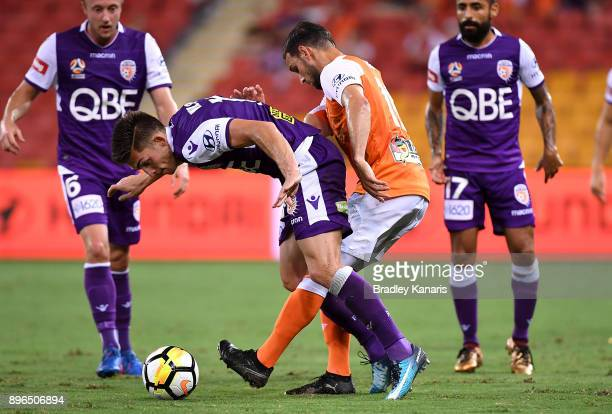 Brandon Wilson of the Glory is pressured by the defence of Jack Hingert of the Roar during the round 11 ALeague match between the Brisbane Roar and...