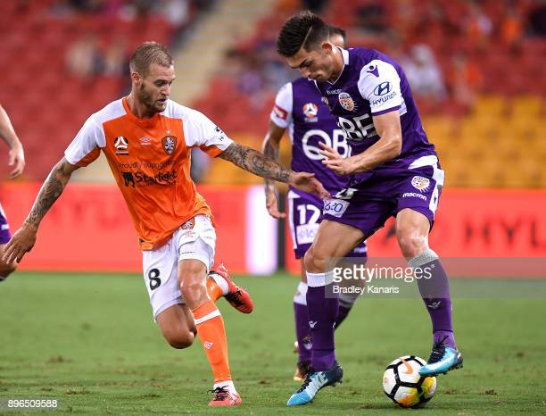 Brandon Wilson of the Glory looks to take on the defence of Jacob Pepper of the Roar during the round 11 ALeague match between the Brisbane Roar and...