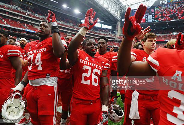 Brandon Wilson of the Houston Cougars celebrates with his teammates after they defeated the Oklahoma Sooners 33-23 during the Advocare Texas Kickoff...