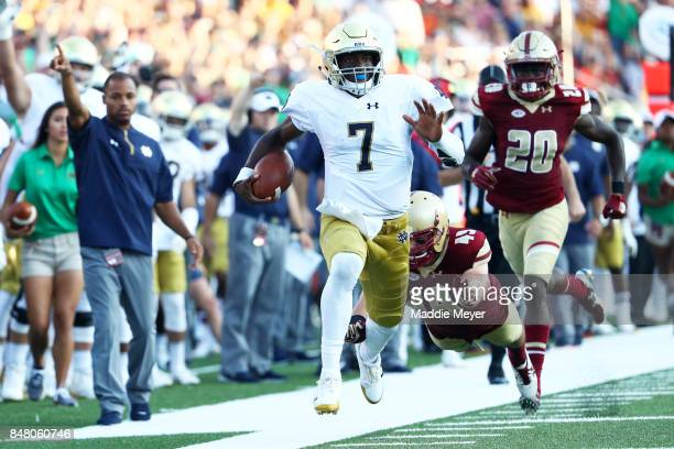 Brandon Wimbush of the Notre Dame Fighting Irish evades a tackle by Kevin Bletzer of the Boston College Eagles to score a touchdown during the second...
