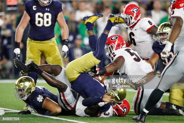 Brandon Wimbush of the Notre Dame Fighting Irish gets sacked by Roquan Smith of the Georgia Bulldogs in the first quarter of a game at Notre Dame...