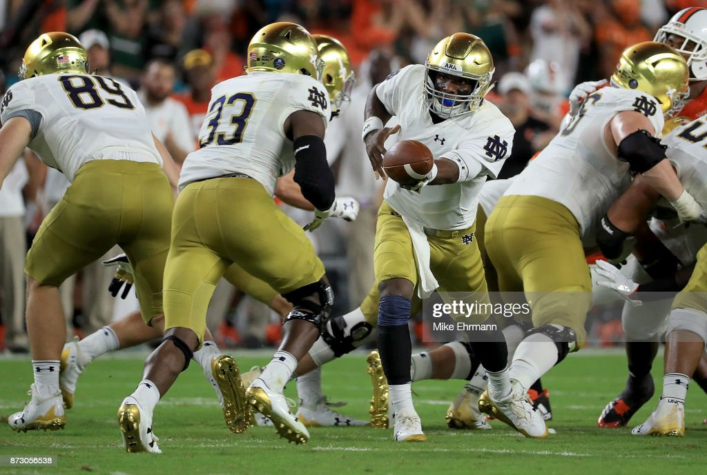 Brandon Wimbush #7 of the Notre Dame Fighting Irish hands off to Josh Adams #33 during a game against the Miami Hurricanes at Hard Rock Stadium on November 11, 2017 in Miami Gardens, Florida.