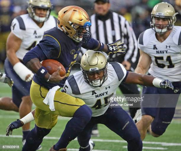 Brandon Wimbush of the Notre Dame Fighting Irish holds off DJ Palmore of the Navy Midshipmen at Notre Dame Stadium on November 18 2017 in South Bend...