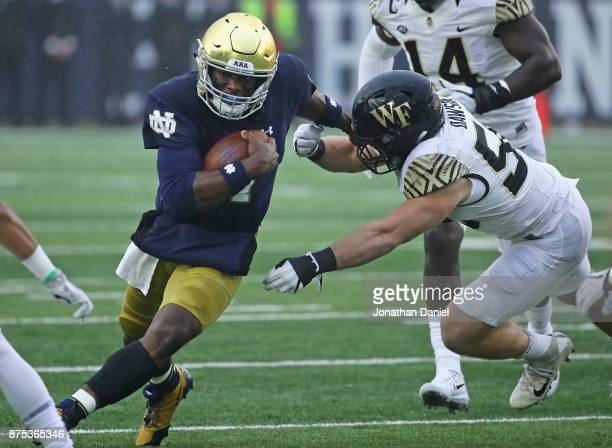 Brandon Wimbush of the Notre Dame Fighting Irish holds off Grant Dawson of the Wake Forest Demon Deacons as he runs for a first down at Notre Dame...