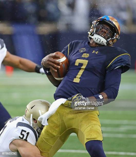 Brandon Wimbush of the Notre Dame Fighting Irish is tackeld by Winn Howard of the Navy Midshipmen at Notre Dame Stadium on November 18 2017 in South...
