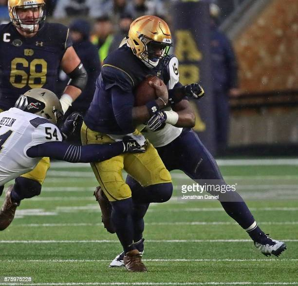 Brandon Wimbush of the Notre Dame Fighting Irish is tackled by Taylor Heflin against the Notre Dame Fighting Irish DJ Palmore of the Navy Midshipmen...
