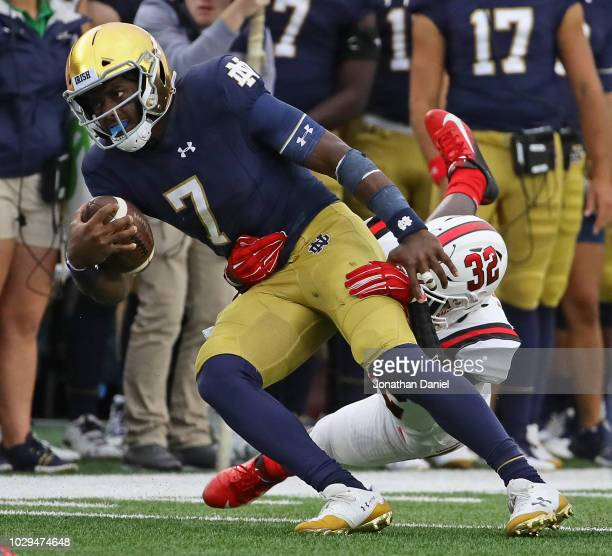 Brandon Wimbush of the Notre Dame Fighting Irish is taken down by Jeremiah Jackson of the Ball State Cardinals at Notre Dame Stadium on September 8...
