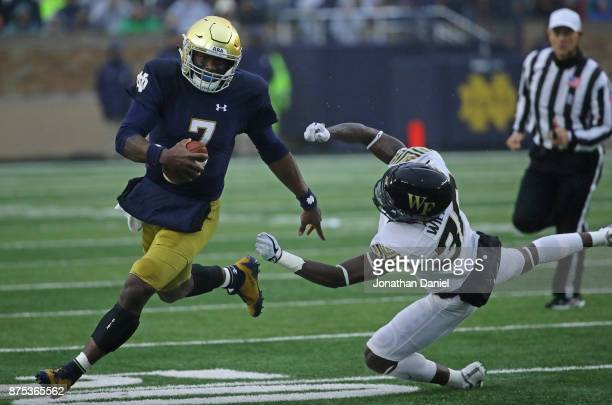 Brandon Wimbush of the Notre Dame Fighting Irish moves past Ja'Cquez Williams of the Wake Forest Demon Deacons at Notre Dame Stadium on November 4...