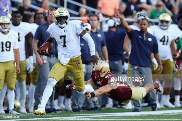 Brandon Wimbush of the Notre Dame Fighting Irish rushes for 46yards as Kevin Bletzer of the Boston College Eagles attempts to tackle him during the...