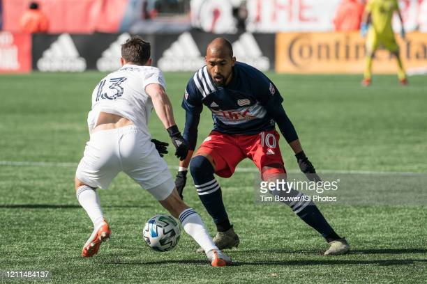 Brandt Bronico of Chicago Fire changes direction to avoid Teal Bunbury of New England Revolution during a game between Chicago Fire and New England...
