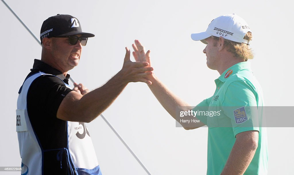 Brandt Snedeker celebrates his three-stroke victory on the 18th green with his caddie Scott Vail during the final round at the AT&T Pebble Beach National Pro-Am at the Pebble Beach Golf Links on February 15, 2015 in Pebble Beach, California.