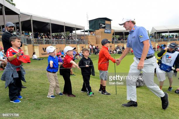 Brandt Snedeker gives high fives to young fans on the 16th hole during the third round of the Valero Texas Open at TPC San Antonio ATT Oaks course on...