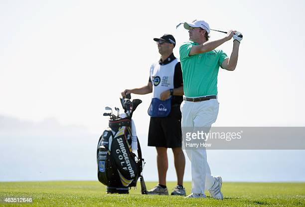 Brandt Snedeker hits his approach shot on the eighth hole as his caddie Scott Vail looks on during the final round of the ATT Pebble Beach National...