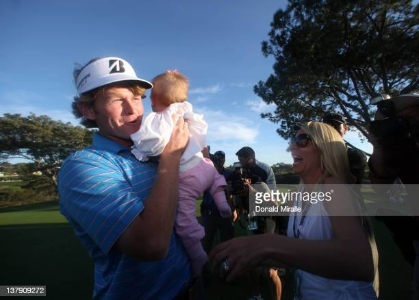 Brandt Snedeker holds 11-month old daughter Lily with wife Mady after his -16 under 2 hole playoff victory during the final round of the Farmers...
