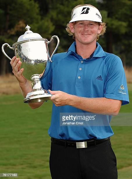 Brandt Snedeker holds the trophy for photographers after winning the Wyndham Championship at Forest Oaks Country Club on August 19, 2007 in...