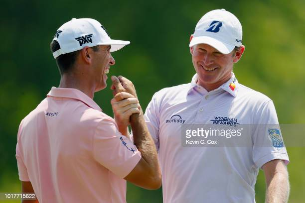 Brandt Snedeker is congratulated by Billy Horschel following a birdie putt on the ninth green during the first round of the Wyndham Championship at...