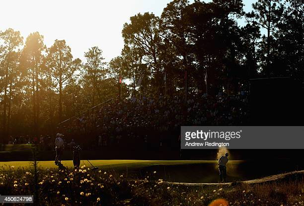 Brandt Snedeker of the United States hits a shot from a greenside bunker on the 16th hole as Kevin Na of the United States looks on during the third...