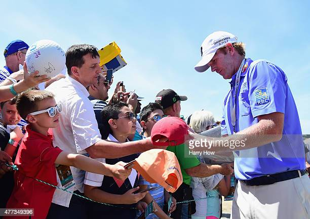 Brandt Snedeker of the United States signs his autograph for fans during a practice round prior to the start of the 115th US Open Championship at...