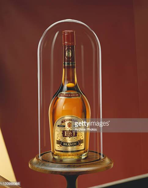 Brandy bottle covered inside glass against red background